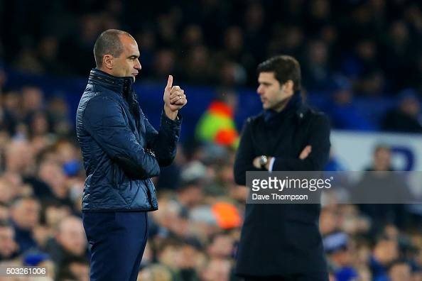 Roberto Martinez manager of Everton gives a thumbs up to his players as Mauricio Pochettino manager of Tottenham Hotspur looks on during the Barclays...