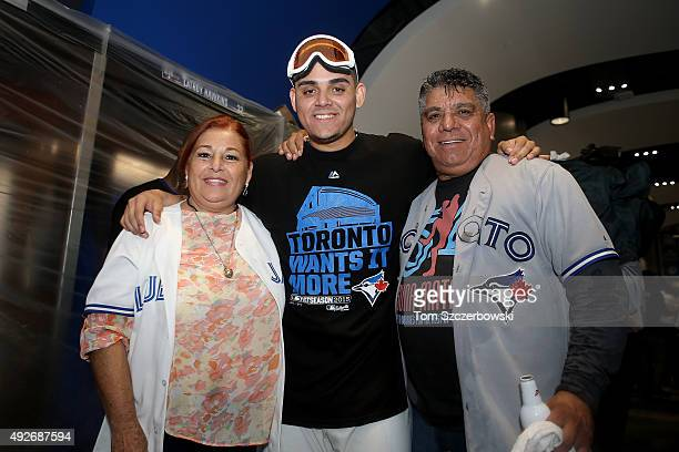 Roberto Osuna of the Toronto Blue Jays and his parents celebrate the 63 win against the Texas Rangers as Ben Revere jumps on top of the pile in game...