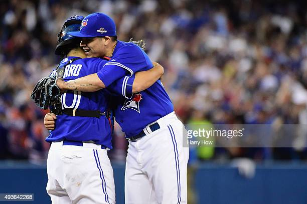 Roberto Osuna of the Toronto Blue Jays celebrates a 71 win over the Kansas City Royals with Dioner Navarro of the Toronto Blue Jays during game five...