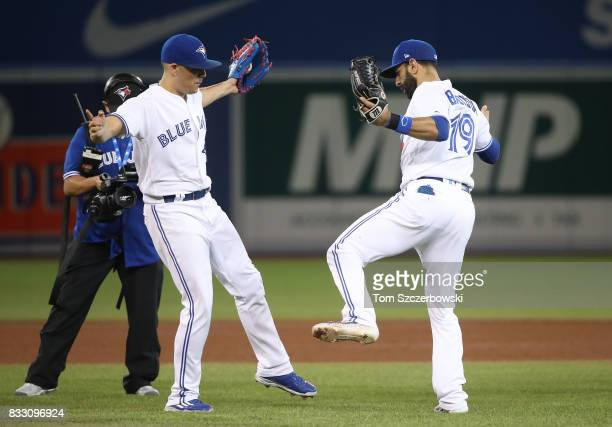 Roberto Osuna of the Toronto Blue Jays celebrates a victory with Jose Bautista during MLB game action against the Tampa Bay Rays at Rogers Centre on...