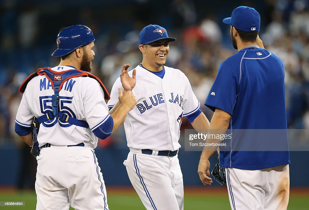 Roberto Osuna #54 of the Toronto Blue Jays celebrates their victory with Russell Martin #55 and Chris Colabello #15 during MLB game action against the Oakland Athletics on August 11, 2015 at Rogers Centre in Toronto, Ontario, Canada.