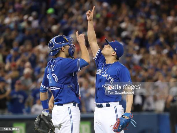 Roberto Osuna of the Toronto Blue Jays celebrates their victory with Luke Maile during MLB game action against the Cincinnati Reds at Rogers Centre...