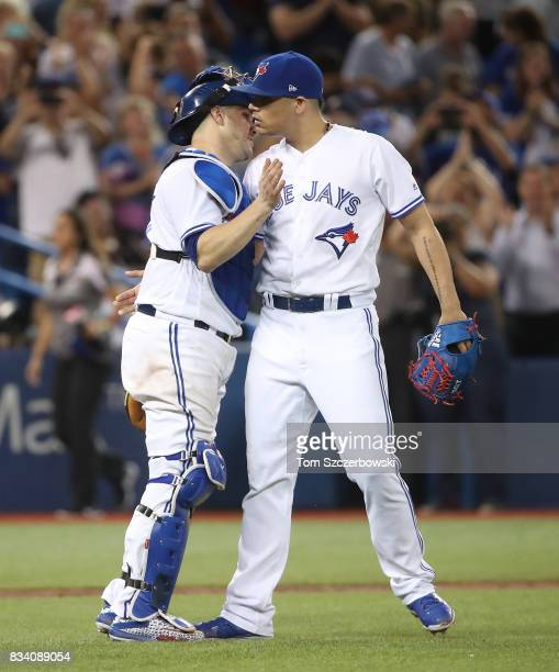 Roberto Osuna of the Toronto Blue Jays celebrates their victory with Miguel Montero during MLB game action against the Tampa Bay Rays at Rogers...
