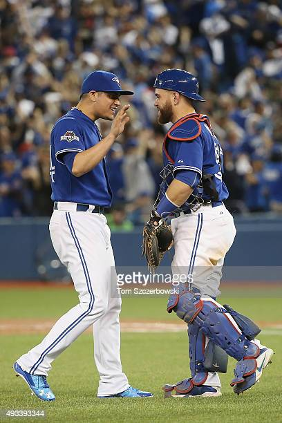 Roberto Osuna of the Toronto Blue Jays celebrates with Russell Martin of the Toronto Blue Jays after defeating the Kansas City Royals 118 in game...