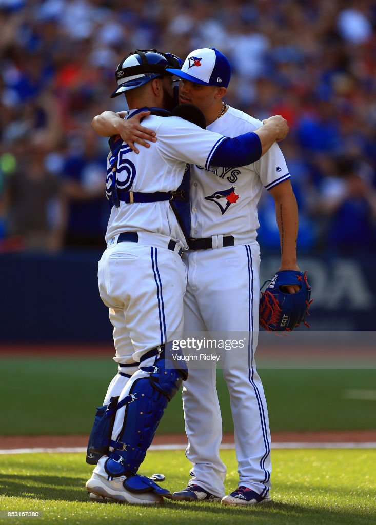 Roberto Osuna #54 of the Toronto Blue Jays hugs Russell Martin #55 after getting the final out in the ninth inning during MLB game action against the New York Yankees at Rogers Centre on September 24, 2017 in Toronto, Canada.