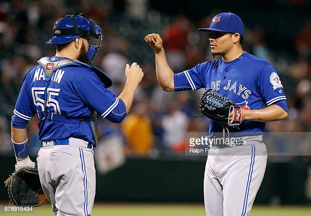 Roberto Osuna of the Toronto Blue Jays is congratulated by catcher Russell Martin after pitching the ninth inning in a 51 victory against the Arizona...