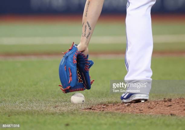 Roberto Osuna of the Toronto Blue Jays picks up the baseball by the edge of the mound as he comes out of the bullpen to pitch the ninth inning during...