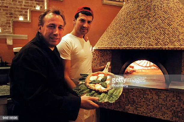 Roberto Paciullo restaurant owner left and Riccardo Rinaldo pizzaiolo pose with a pie of traditional Margherita pizza at Zero Otto Nove Paciullo's...