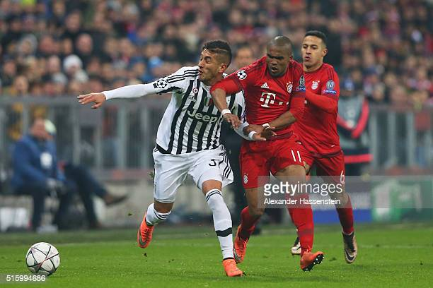 Roberto Pereyra of Juventus and Douglas Costa of Bayern Muenchen compete for the ball during the UEFA Champions League round of 16 second Leg match...