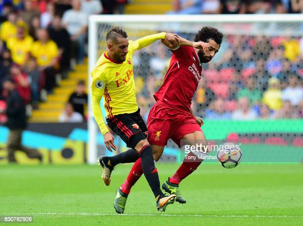 Roberto Pereyra of Watford tackles Mohamed Salah of Liverpool during the Premier League match between Watford and Liverpool at Vicarage Road on...