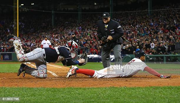 Roberto Perez of the Cleveland Indians is unable to make the tag as Xander Bogaerts of the Boston Red Sox scores a run in the fifth inning during...