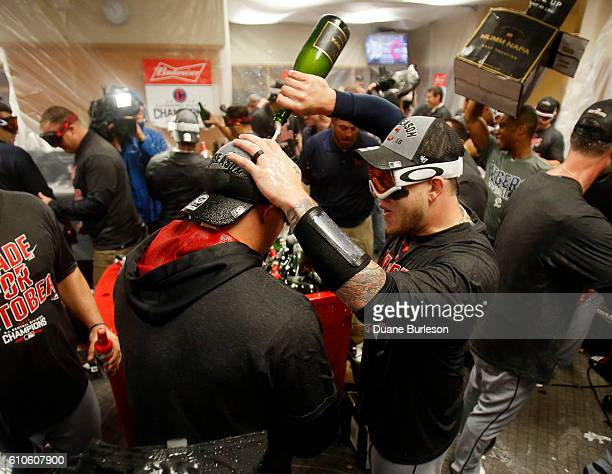 Roberto Perez of the Cleveland Indians pours champagne on a teammate after clinching the Central Division Championship after defeating the Detroit...