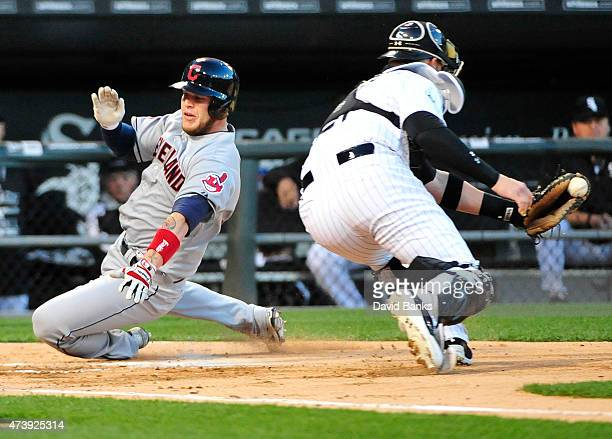 Roberto Perez of the Cleveland Indians scores as Tyler Flowers of the Chicago White Sox makes a late tag during the third inning on May 18 2015 at U...