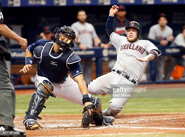 Roberto Perez of the Cleveland Indians slides safely home ahead of the throw to catcher Hank Conger of the Tampa Bay Rays to score on a single by...