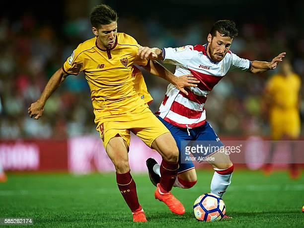 Roberto Roman Triguero of Granada FC competes for the ball with Luciano Vietto of Sevilla FC during a friendly match between Granada FC and Sevilla...