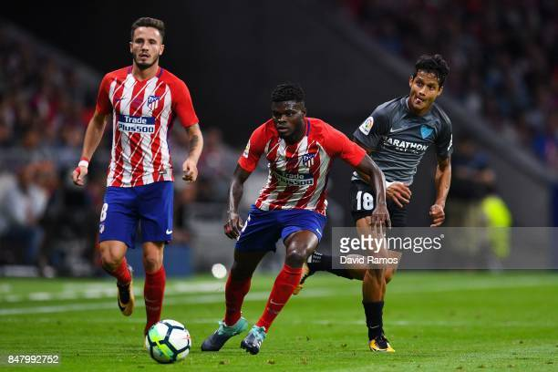 Roberto Rosales of Malaga CF competes for the ball with Thomas Partey of Club Atletico de Madrid during the La Liga match between Atletico Madrid and...