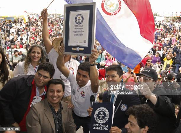Roberto Servin president of the Terere Asocciation holds up the Guinness World Record certificate for the largest 'terere' round of the world in...