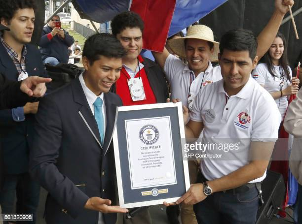 Roberto Servin president of the Terere Asocciation receives a certificate from Carlos Tapia Guinness World Record representative after the Guinness...