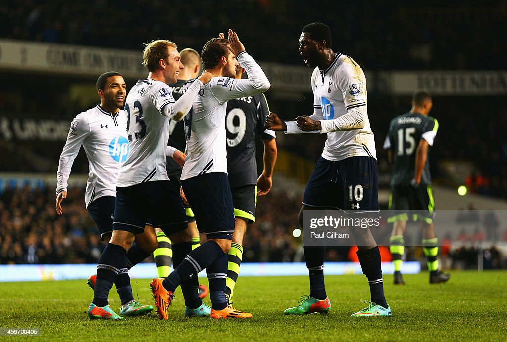 Roberto Soldado of Tottenham Hotspur is congratulated by team mates including Emmanuel Adebayor (R) and Christian Eriksen after scoring from the penalty spot during the Barclays Premier League match between Tottenham Hotspur and Stoke City at White Hart Lane on December 29, 2013 in London, England.