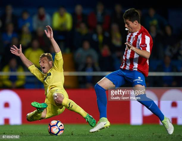 Roberto Soldado of Villarreal is tackled by Jorge Mere of Real Sporting de Gijon during the La Liga match between Villarreal CF and Real Sporting de...