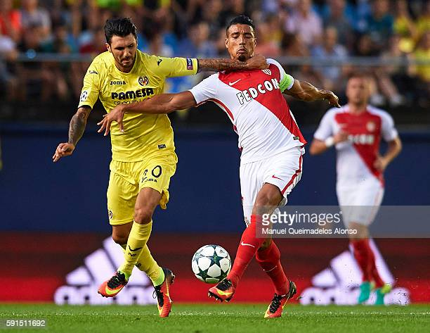 Roberto Soriano of Villarreal competes for the ball with Nabil Dirar of Monaco during the UEFA Champions League playoff first leg match between...