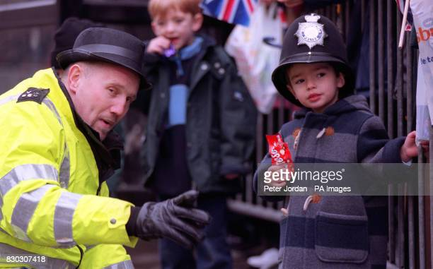PC Roberts from Kingston swops hats with Felix aged 3 from Sydenham Hill as they watch the Millennium Parade in London Giant inflatables joined...