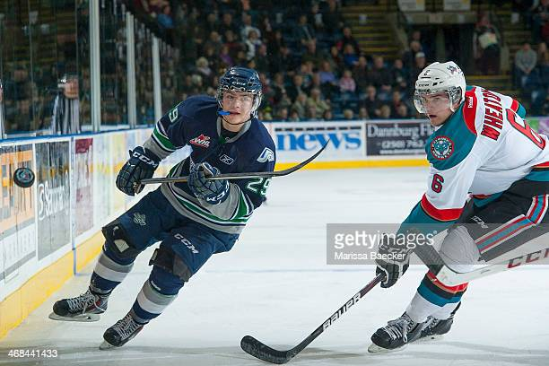 Roberts Lipsbergs of the Seattle Thunderbirds passes the puck as Mitchell Wheaton of the Kelowna Rockets comes in for the check during second period...