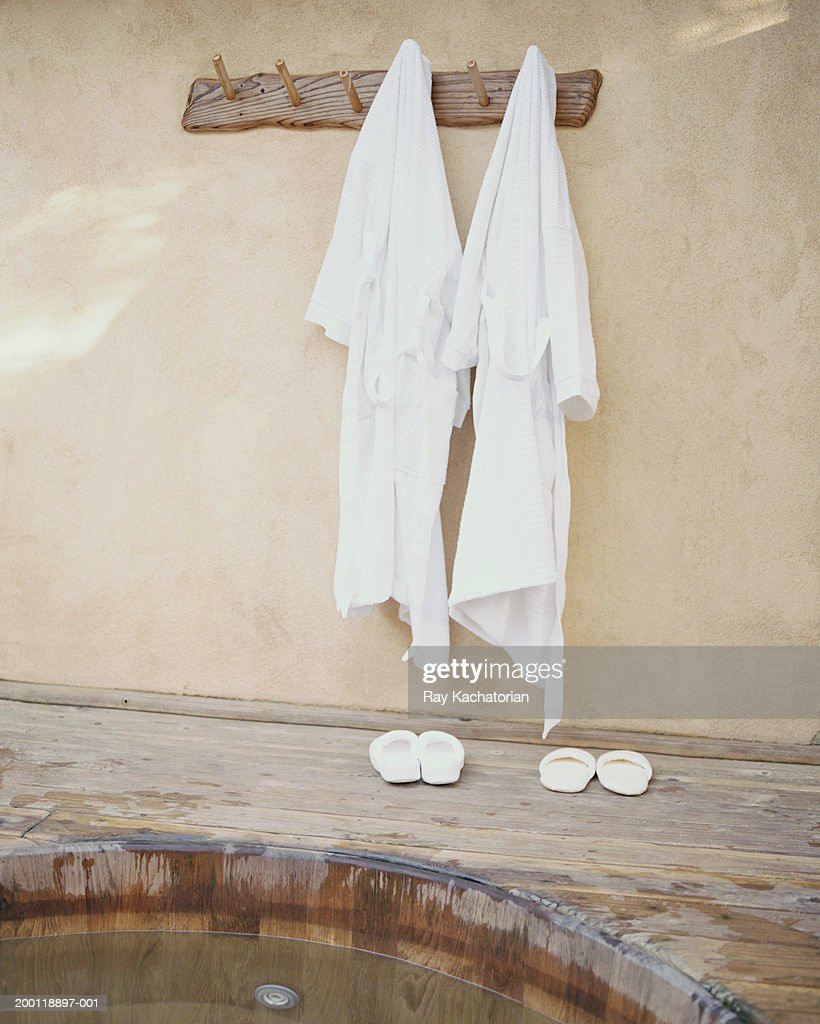 Robes hanging on wall by hot tub