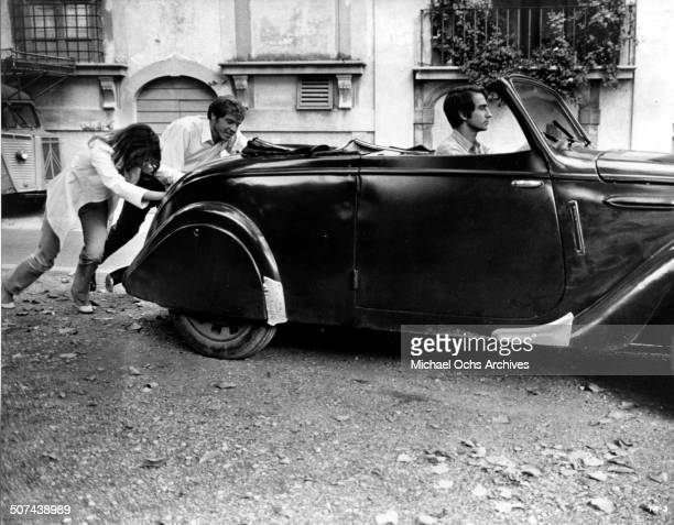 Robie Porter and Charlotte Rampling push Sam Waterston trying to start the car in a scene from the movie 'Three' circa 1967