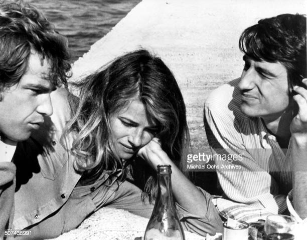 Robie Porter Charlotte Rampling and Sam Waterston picnic by a sea wall in a scene from the movie 'Three' circa 1967
