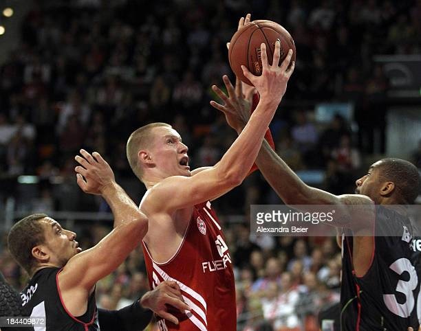 Robin Benzing of Bayern Muenchen fights for the ball with Kyle Weems and Ronald Burrell of medi Bayreuth during the Basketball Bundesliga match...