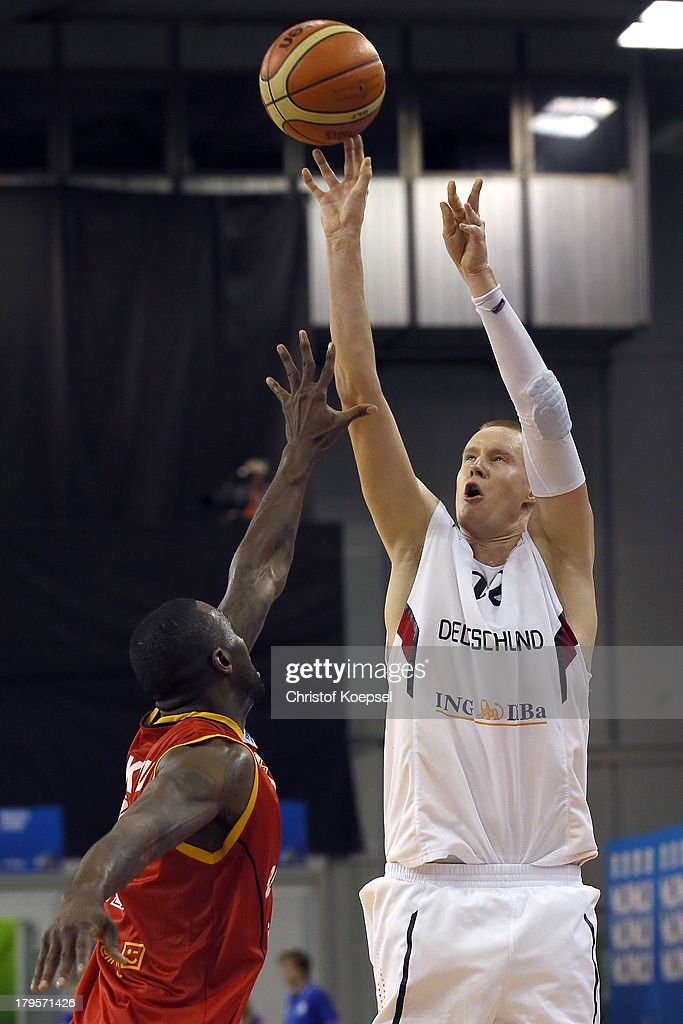 Robin Benzing of Gemany shoots over Wen Mukubu of Belgium (L) during the FIBA European Championships 2013 first round group A match between Germany and Belgium at Tivoli Arena on September 5, 2013 in Ljubljana, Slovenia.