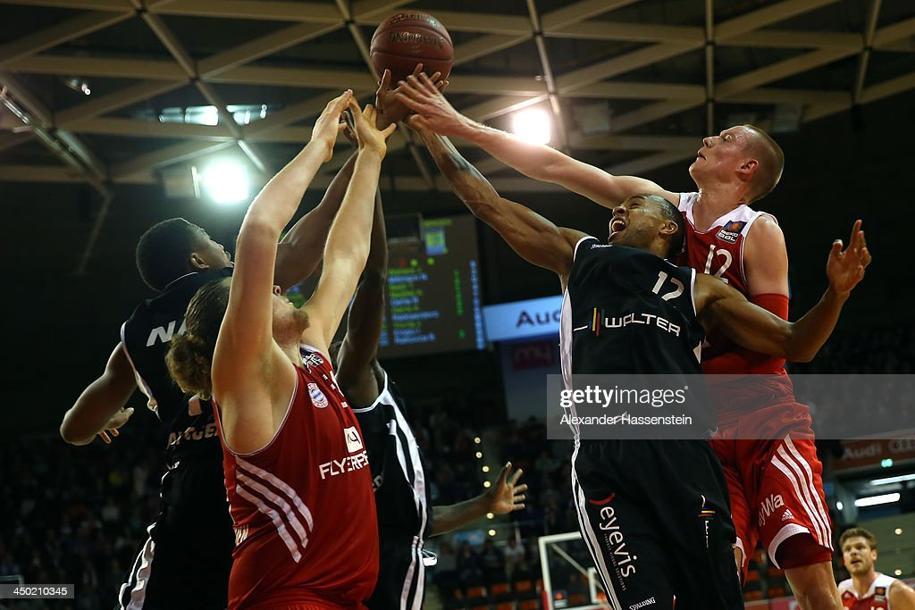 Robin Benzing (R) of Muenchen and his team mate John Bryant (2nd L) battle for the ball with Tyrone Nash (L) of Tuebingen and his team mate Alex Harris (2nd R) during the Beko Basketball Bundesliga match between FC Bayern Muenchen and WALTER Tigers Tuebingen at Audi-Dome on November 17, 2013 in Munich, Germany.