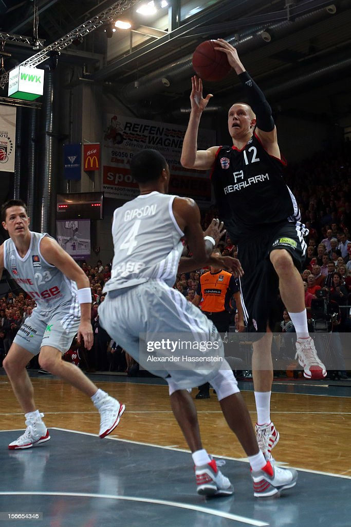 Robin Benzing (C) of Muenchen shoots against Sergio Gipson of Bamberg during the Beko Basketball match between Brose Bamberg and FC Bayern Muenchen at Stechert Arena on November 18, 2012 in Bamberg, Germany.
