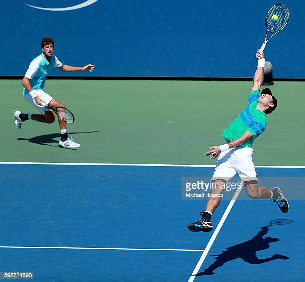 Robin Haase of Netherlands and Artem Sitak of New Zealand in action against Nicolas Mahut and PierreHugues Herbert of France during his second round...