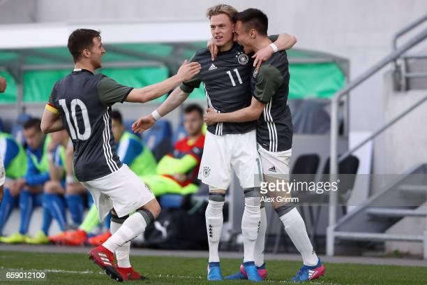 Robin Hack celebrates his team's first goal with team mate Dominik Franke and Salih Oezcan during the UEFA Elite Round match between Germany U19 and...