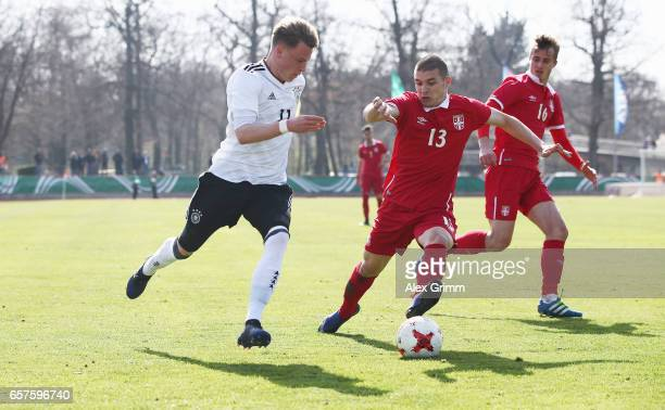 Robin Hack of Germany is challenged by Jovica Blagojevic and Marko Pantic of Serbia during the UEFA Elite Round match between U19 Germany and U19...