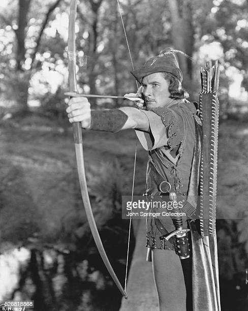 Robin Hood steadies his bow in Warner Brothers' film The Adventures of Robin Hood