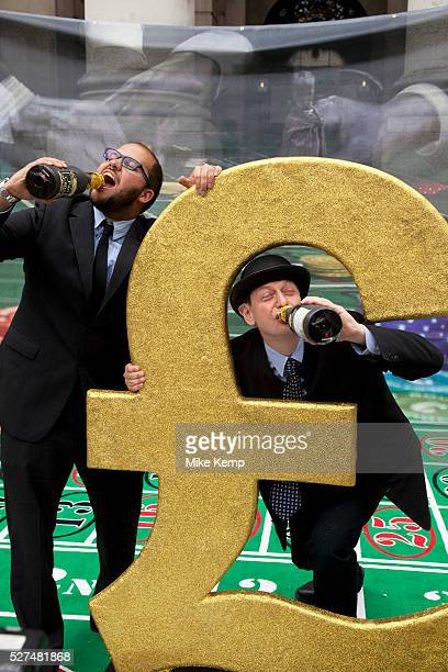 Robin Hood Tax supporters pretend to be greedy bankers drinking champagne during a protest at the Royal Exchange near the Bank of England in the City...