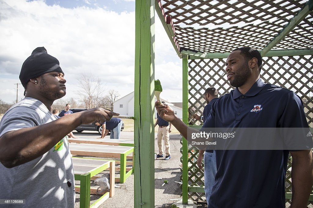 Robin Hopkins shows Scoop Jardine of the Tulsa 66ers how to paint a pergola during the NBA D-League community relations event at A New Leaf, a non-profit that employs adults with developmental disabilities, on March 27, 2014 in Broken Arrow, Oklahoma.