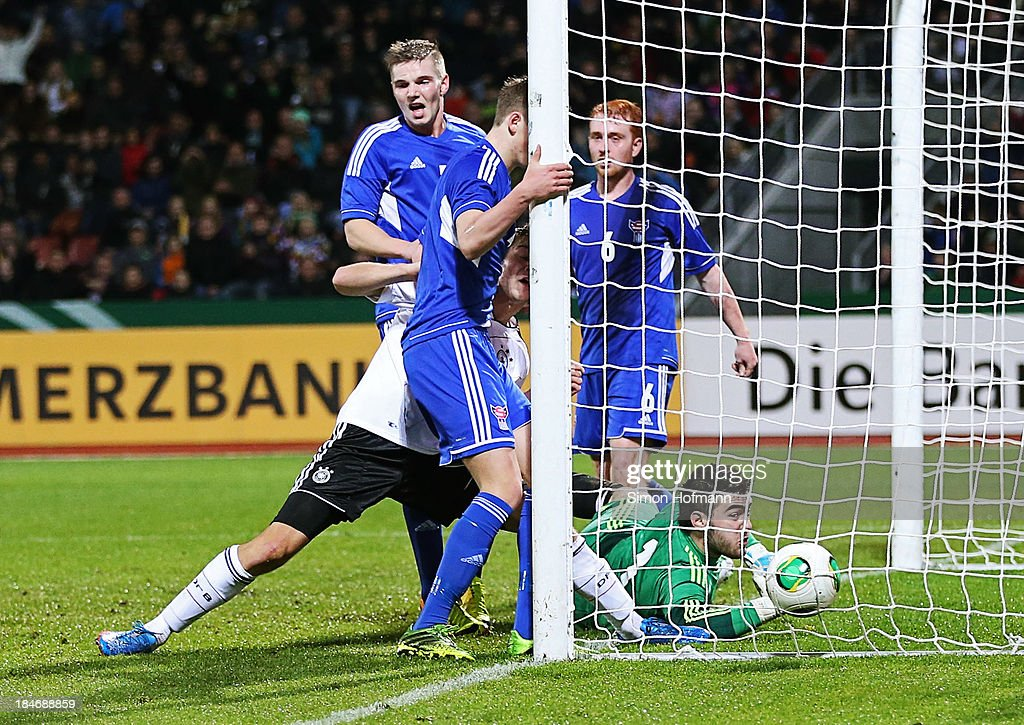 Robin Knoche of Germany scores his team's first goal against goalkeeper Teitur Gestson of Faroe Islands during the 2015 UEFA European U21 Championships Qualifying Group Six match between Germany U21 and Faroe Islands U21 at Auestadion on October 15, 2013 in Kassel, Germany.
