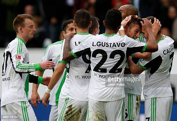Robin Knoche of Wolfsburg celebrates with his team mates after scoring his team's third goal during the Bundesliga match between at Volkswagen Arena...