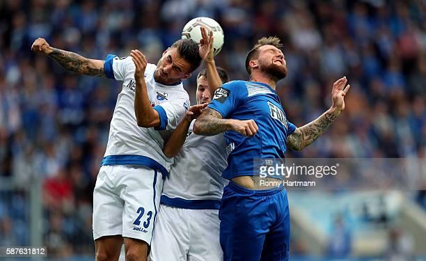 Robin Krausse and Koen van der Biezen of Paderborn head for the ball with Jan Loehmannsroeben of Magdeburg during the Third League match between 1 FC...