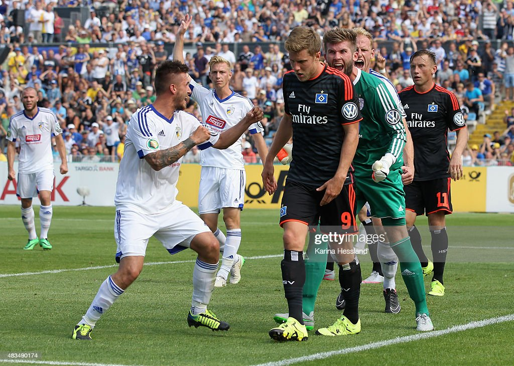 Robin Krausse Goalkeeper Raphael Koczor and Justin Gerlach of Jena look happy Sven Schipplock of Hamburger SV looks dejected during the First Round...