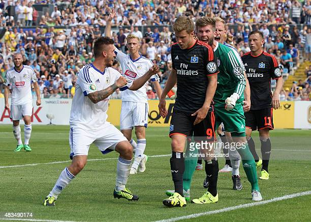 Robin Krausse Goalkeeper Raphael Koczor and Justin Gerlach of Jena look happy Sven Schipplock of Hamburger SV looks dejected during the First Round...