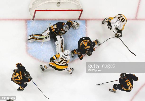 Robin Lehner and Josh Gorges of the Buffalo Sabres defend against Patric Hornqvist and Sidney Crosby of the Pittsburgh Penguins during an NHL game at...