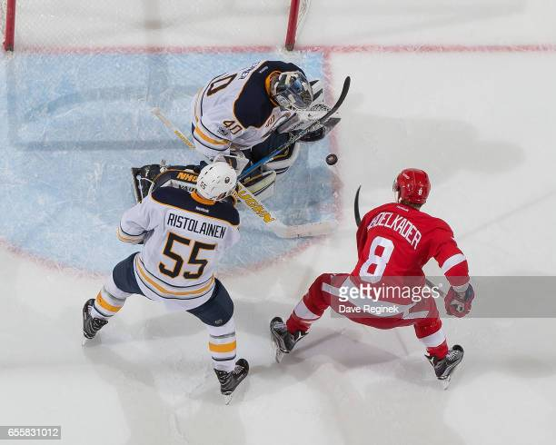 Robin Lehner of the Buffalo Sabres makes a save as teammate Rasmus Ristolainen and Justin Abdelkader of the Detroit Red Wings look for the rebound...