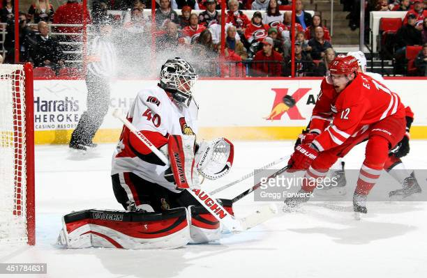 Robin Lehner of the Ottawa Senators eyes a shot as Eric Staal of the Carolina Hurricanes skates hard to the net during their NHL game at PNC Arena on...