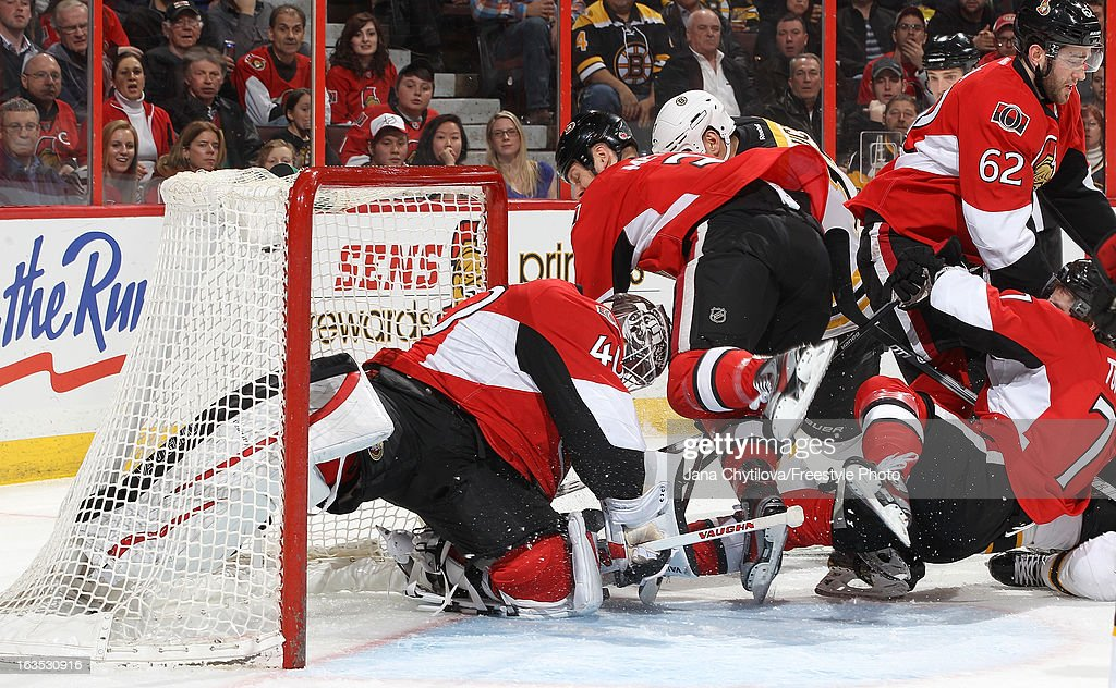 Robin Lehner #40 of the Ottawa Senators gets his pad against the post to make a save as team mate Marc Methot #3 defends against Milan Lucic #17 of the Boston Bruins, during an NHL game at Scotiabank Place, on March 11, 2013 in Ottawa, Ontario, Canada.