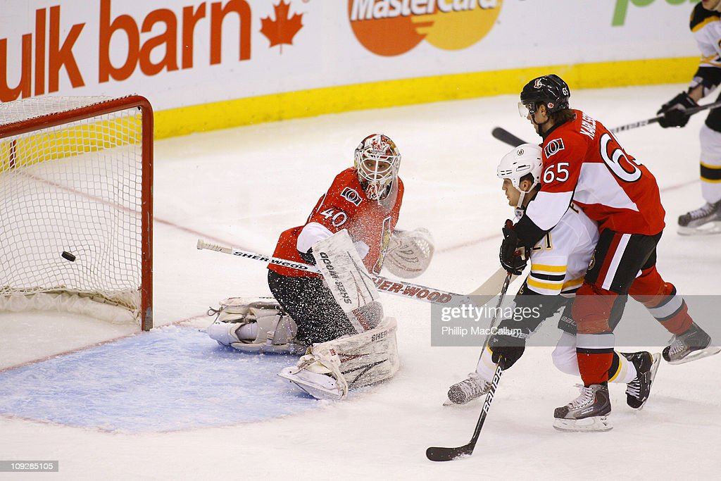 Robin Lehner of the Ottawa Senators looks back into his net to see the puck while teammate Erik Karlsson tries to tie up Andrew Ference of the Boston...